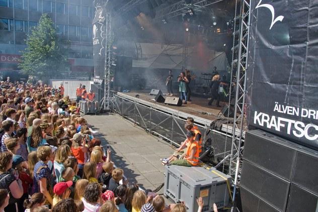 Publik och scen. Kameran upphissad på 150cm enbensstativ. Bilden består av fem delar. Scenen, avgränsningen framför, publiken, trädet och den svarta ytan till höger.