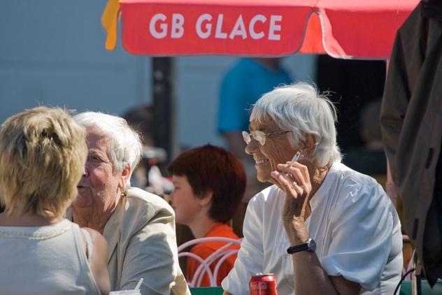 Rökande kvinna glassar i solen. Denna bild tog jag för att kvinnan såg så skönt avslappnad ut med cigaretten. GB Glace-parasollet tog jag med för att göra bilden lite klurigare.