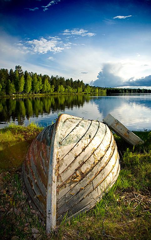 Båtens sista sommar. Tagen med 18mm vidvinkel. Även denna bild består av fem delar. Himlen, kilformen av träden, vattnet, gräset och själva båten.